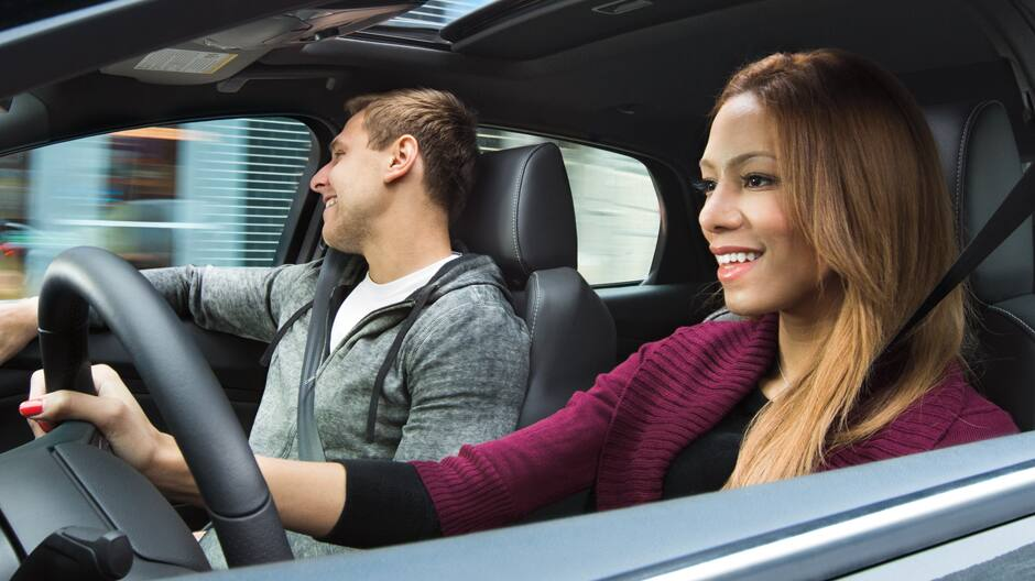 Driver and passenger smiling inside Ford vehicle
